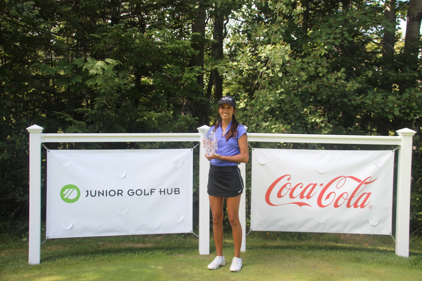 Melena Barrientos with trophy in front of Junior Golf Hub and CocaCola Sign - 2020 - Coca-Cola Junior Championship at Sugarloaf presented by Junior Golf Hub.JPG